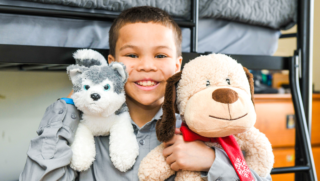 Young smiling boy hugs two stuffed animals