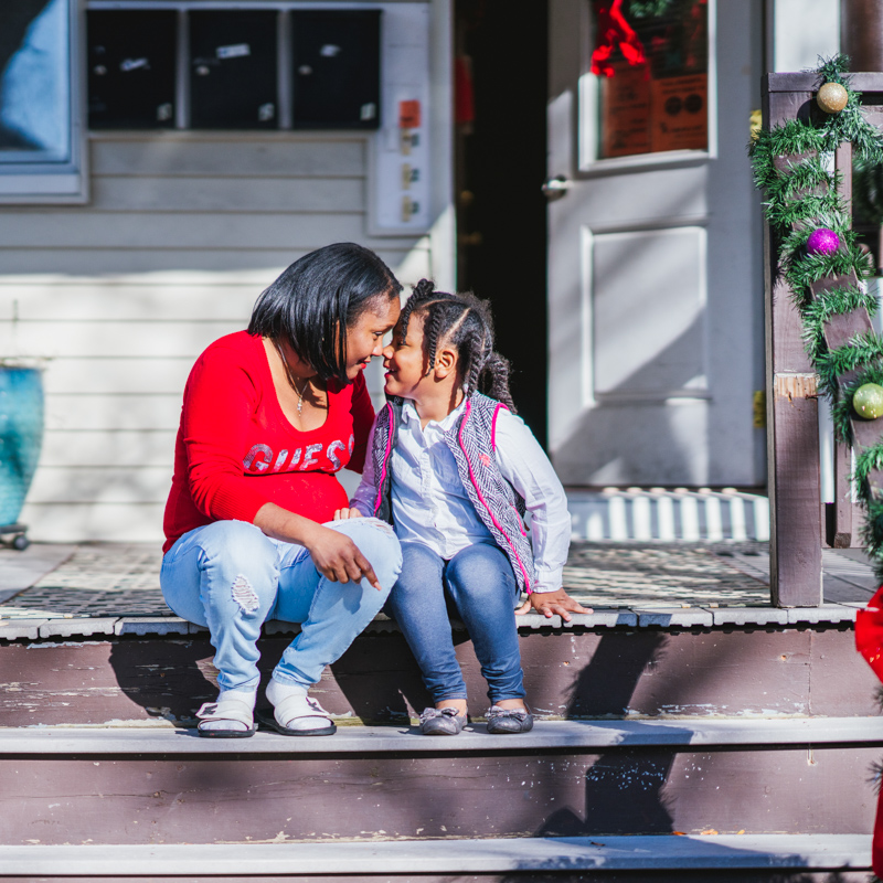 Woman and young girl touch foreheads on porch