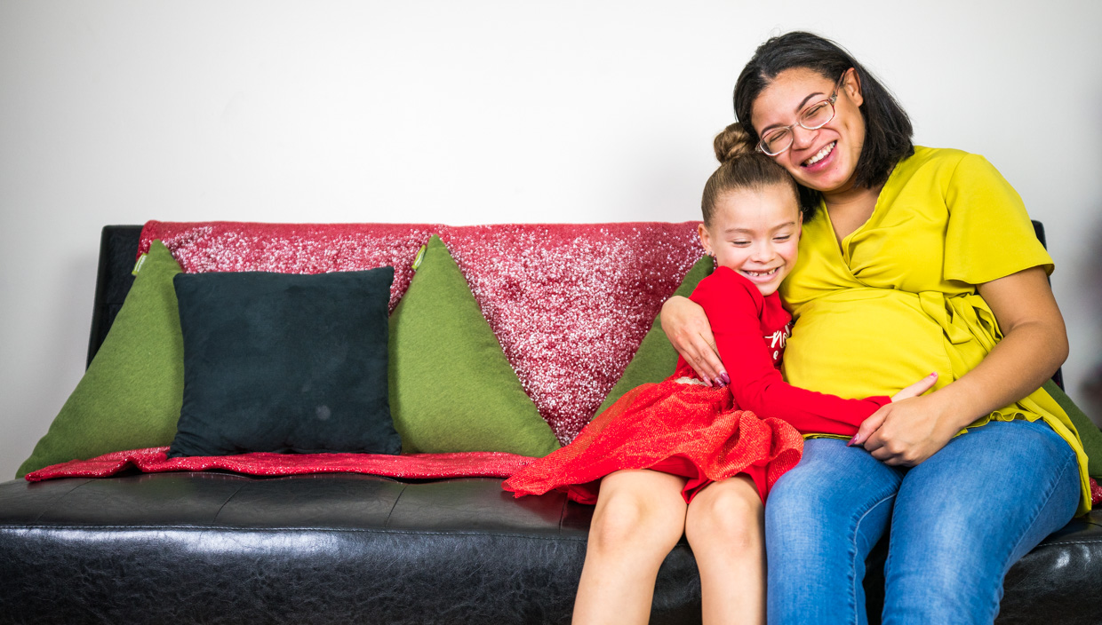 Mother and daughter hug while sitting on couch