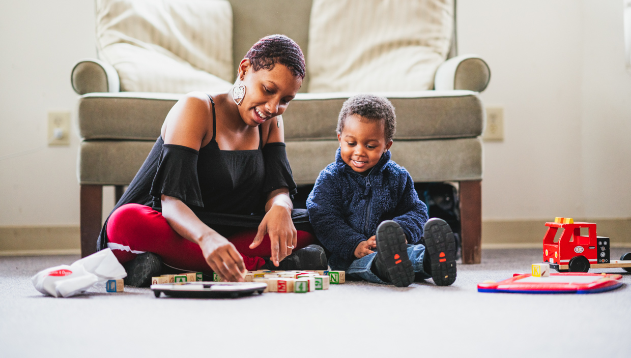 Woman and child play with blocks on the floor