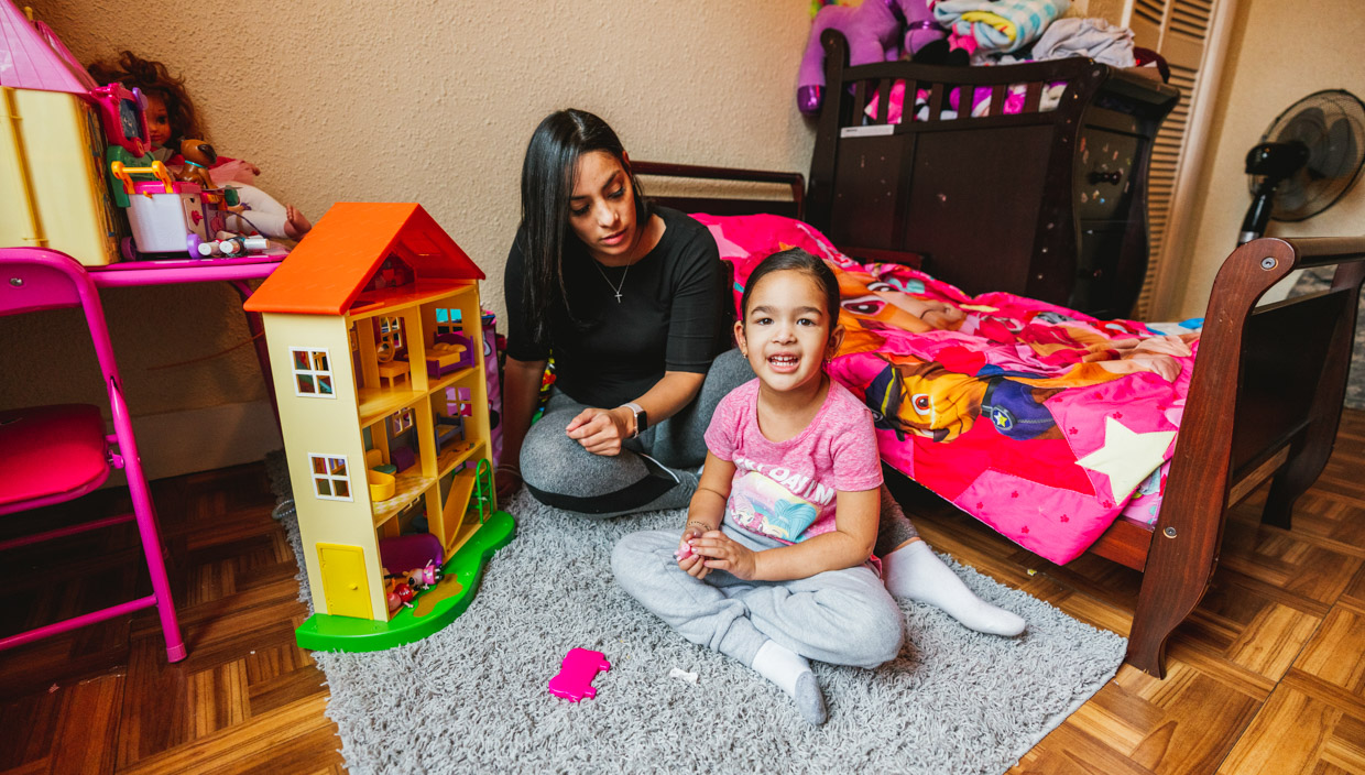 Woman and child play with dollhouse on bedroom floor