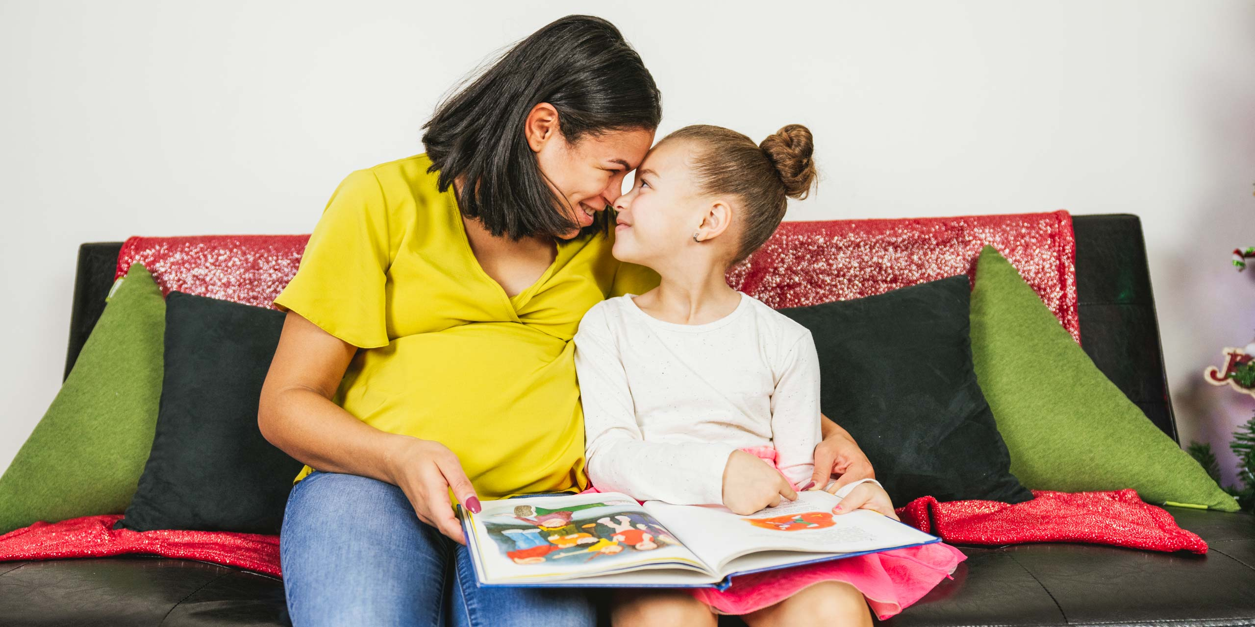 Woman and young girl touch foreheads while reading book